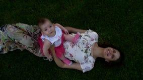 La hija se está sentando en su mamá y sonrisa