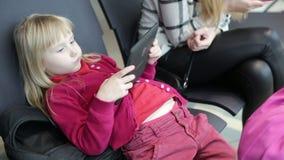 La hija y la madre están mecanografiando en la tableta y el teléfono móvil, esperando un avión metrajes