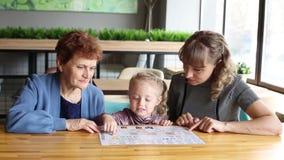 La hija y la nieta de la abuela que miran el menú en un café metrajes