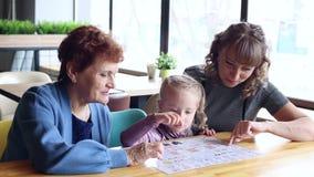 La hija y la nieta de la abuela que miran el menú en un café almacen de video