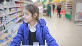 La hija y su madre están haciendo compras en el supermercado Pequeña señora auxiliar metrajes
