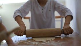 La hija y un hijo son toda en las camisetas blancas en la misma tabla que prepara una empanada fines de semana con la familia rol almacen de video