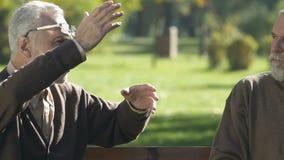 La historia que dice masculina envejecida al amigo en parque, discusión de las noticias, pensionistas habla almacen de metraje de vídeo