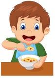 La historieta del muchacho está teniendo cereal para el desayuno Fotos de archivo libres de regalías