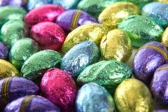 La hoja cubrió los mini huevos de chocolate Imagen de archivo libre de regalías