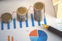 la hoja de cálculo financiera de la acción de actividades bancarias con la pila de moneda, contiene Fotos de archivo