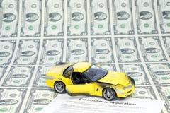 La hoja de dos billetes de dólar y el coche con seguro forman Fotografía de archivo libre de regalías