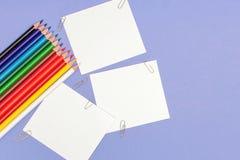 La hoja de espacios en blanco de papeles y el color dibujaron a l?piz en el fondo violeta para los proyectos y los avisos, copian fotos de archivo libres de regalías