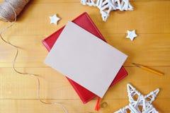 La hoja de papel de Kraft del fondo de la Navidad con el lugar para su texto y la Navidad blanca protagonizan el fondo de madera  Foto de archivo libre de regalías