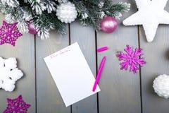 La hoja de papel, los lápices rosados y las decoraciones de la Navidad en un fondo de madera Concepto de Año Nuevo y de la Navida Fotografía de archivo libre de regalías
