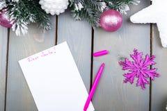 La hoja de papel, los lápices rosados y las decoraciones de la Navidad en un fondo de madera Concepto de Año Nuevo y de la Navida Imagenes de archivo
