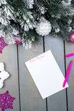 La hoja de papel, los lápices rosados y las decoraciones de la Navidad en un fondo de madera Concepto de Año Nuevo y de la Navida Fotos de archivo
