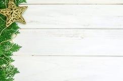 La hoja del pino con la decoración de la bola de la estrella y de la Navidad del oro amarillo en el tablero de madera blanco con  Foto de archivo