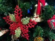 La hoja roja y la campana de oro con la cinta roja adornan en el árbol de navidad fotos de archivo libres de regalías