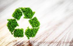 La hoja verde fresca recicla símbolo en el escritorio de madera con empañado detrás Imagenes de archivo