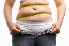 La holding grassa della donna lei apre la chiusura lampo dei jeans Fotografie Stock