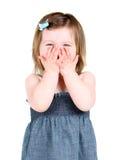 La holding sveglia della bambina lei cosegna la sua bocca Immagine Stock