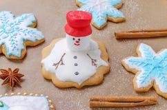 La hornada del pan de jengibre de la Navidad le gusta derretir el muñeco de nieve, los copos de nieve y la harina como nieve Imágenes de archivo libres de regalías