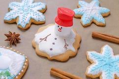 La hornada del pan de jengibre de la Navidad le gusta derretir el muñeco de nieve y los copos de nieve Imagen de archivo