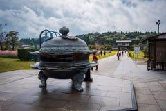 La hornilla de incienso viejo-japonesa del estilo para rogar a Ushiku Daibutsu, es la estatua más grande de Buda del mundo, Japón fotos de archivo