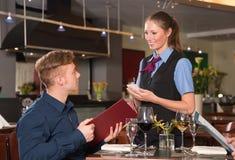 La huésped en un restaurante pide la comida del menú Foto de archivo libre de regalías