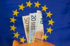 La hucha con las notas euro, UE señala por medio de una bandera en el fondo Fotos de archivo libres de regalías