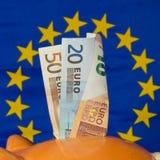 La hucha con las notas euro, UE señala por medio de una bandera en el fondo Foto de archivo libre de regalías