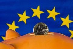 La hucha con una moneda euro, UE señala por medio de una bandera en fondo Foto de archivo libre de regalías