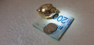 La hucha se coloca en luz del punto en billete de banco doblado de doscientos shekels imagenes de archivo