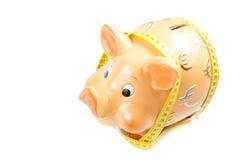 La hucha y la cinta de la medida, concepto para el negocio y ahorran el dinero Fotografía de archivo libre de regalías