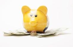 La hucha y la pila amarillas de monedas del dinero aisladas sobre el fondo blanco sortean efectivo del dólar debajo de él Imágenes de archivo libres de regalías