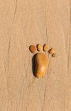 La huella compuso de piedras en la arena Foto de archivo