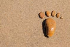 La huella compuso de piedras en la arena Fotos de archivo libres de regalías