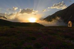 La hutte de montagne sur le champ se développant en soleil rayonne au coucher du soleil Photographie stock libre de droits