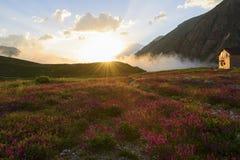 La hutte de montagne sur le champ se développant en soleil rayonne au coucher du soleil Image stock