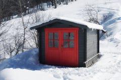 La hutte rouge vive sur la neige a couvert la montagne en hiver Image libre de droits