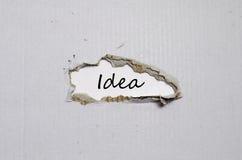 La idea de la palabra que aparece detrás del papel rasgado Fotos de archivo libres de regalías