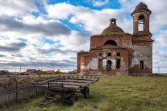 La iglesia arruinada abandonada en el campo cerca es un carro del caballo, cielo soleado del día de verano fotografía de archivo