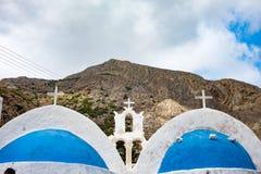 La iglesia blanca con el azul cubre con una cúpula la playa de Kamari, Grecia Foto de archivo libre de regalías