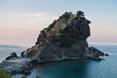 La iglesia de Agios Ioannis Kastri en una roca en la puesta del sol, famosa de las escenas de la película de Mia de la mama, isla Imagen de archivo libre de regalías