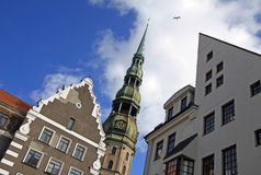 La iglesia de San Pedro en Riga con las casas vecinas Fotos de archivo