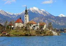 La iglesia en la isla del lago SANGRÓ en ESLOVENIA y el moun nevoso Foto de archivo libre de regalías
