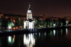 La iglesia hermosa con la iluminación en la noche, luces reflejó en el agua Vista de la ciudad Dnepr Imágenes de archivo libres de regalías
