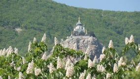 La iglesia ortodoxa en Foros se opone en una montaña, a un contexto de castañas florecientes almacen de video