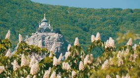 La iglesia ortodoxa en Foros se opone en una montaña, a un contexto de castañas florecientes metrajes