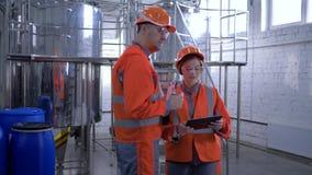 La igualdad de género en la industria pesada, mujer sonriente con el especialista de sexo masculino de la fábrica en cascos sacud metrajes