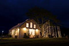 La iluminación hermosa adornó la granja en la noche Imagenes de archivo