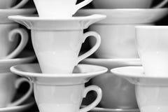 La imagen blanco y negro de las tazas y de los platillos blancos arregló en las filas Imágenes de archivo libres de regalías