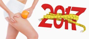 la imagen compuesta 3D de la mujer del ajuste que exprime la grasa en muslo como ella sostiene la naranja Fotografía de archivo