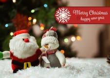 La imagen compuesta de Digital de la Feliz Navidad y de la Feliz Año Nuevo desea con Papá Noel y el muñeco de nieve Imagen de archivo